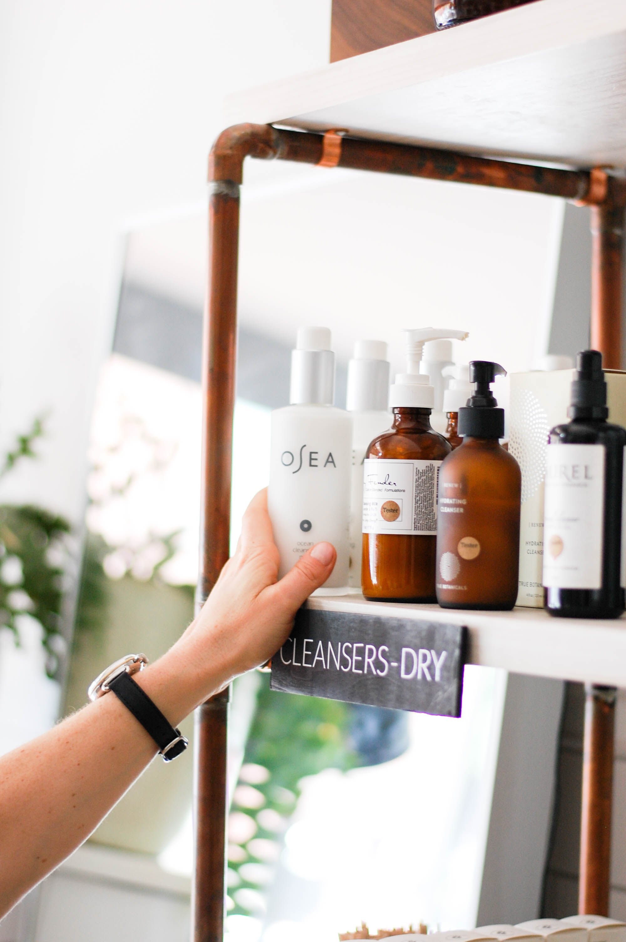 Kerri Axelrod grabbing OSEA Ocean Cleansing Milk, a key part in her skincare routine